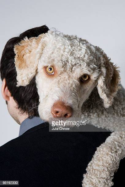 Portrait of a man holding a dog, rear view