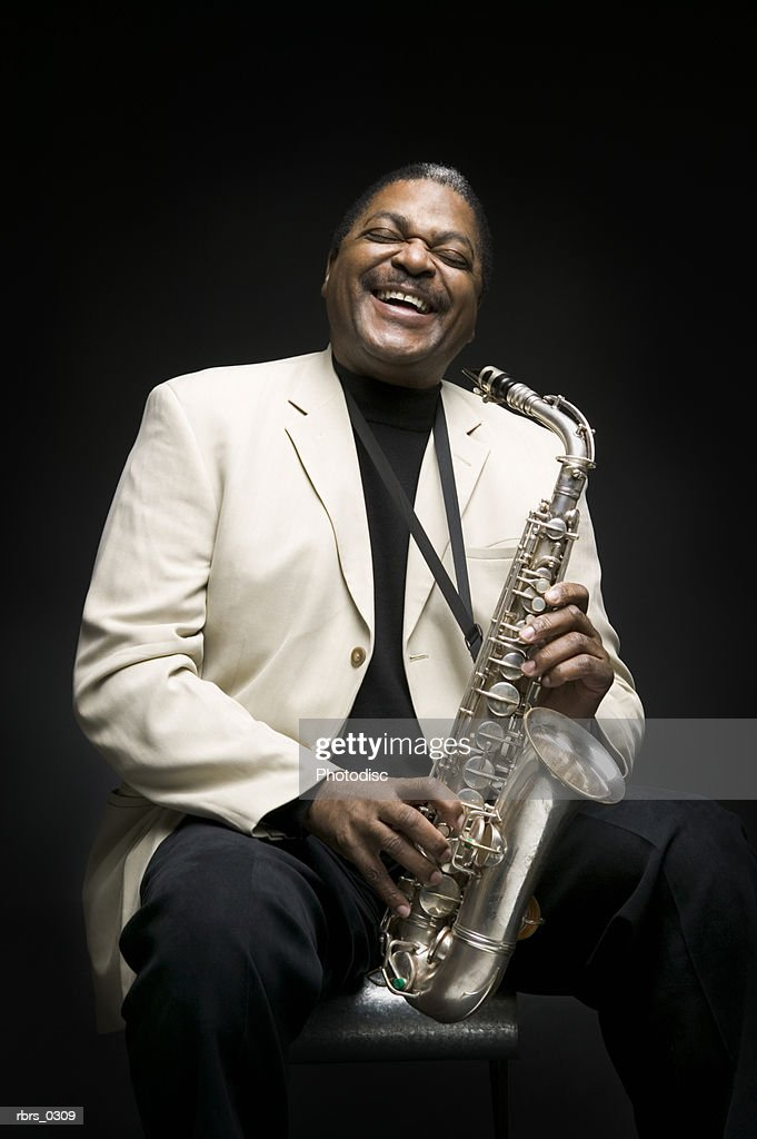 Portrait of a man holding a saxophone : Stock Photo