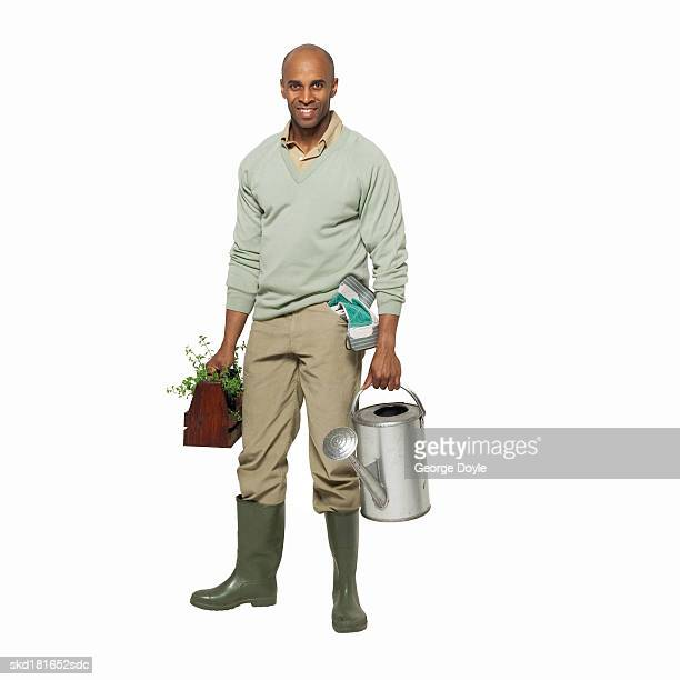 portrait of a man holding a watering can and plant
