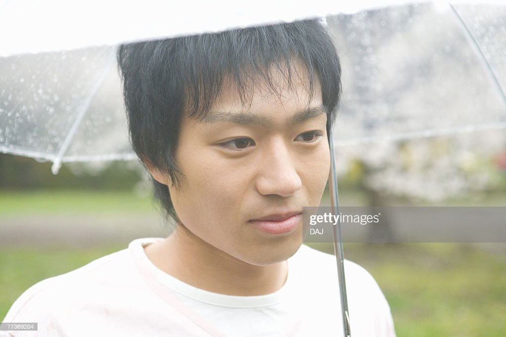 Portrait of a man holding an umbrella, front view, Japan : Photo