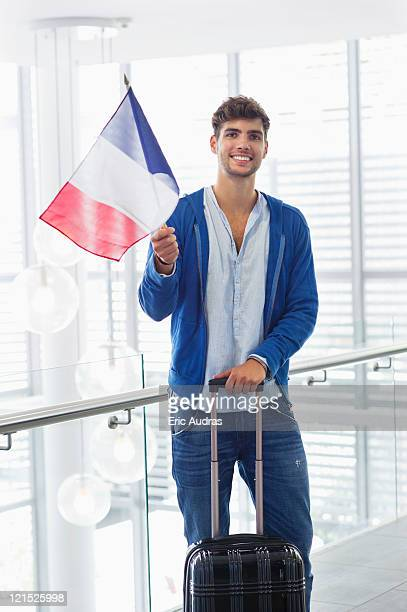 Portrait of a man holding French flag and a suitcase at an airport