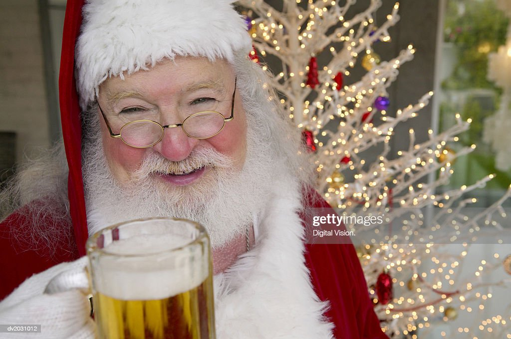 Portrait of a Man in a Father Christmas Outfit Holding a Glass of Beer : Stock Photo