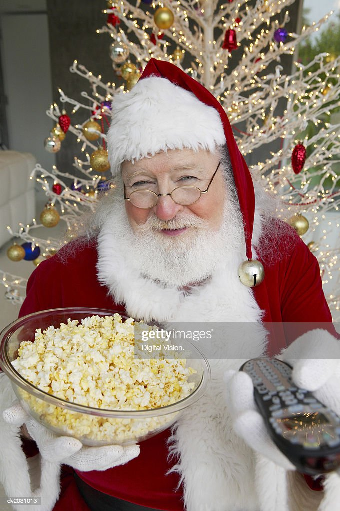 Portrait of a Man in a Santa Costume Holding a Bowl of Popcorn and a Remote Control : Stock Photo