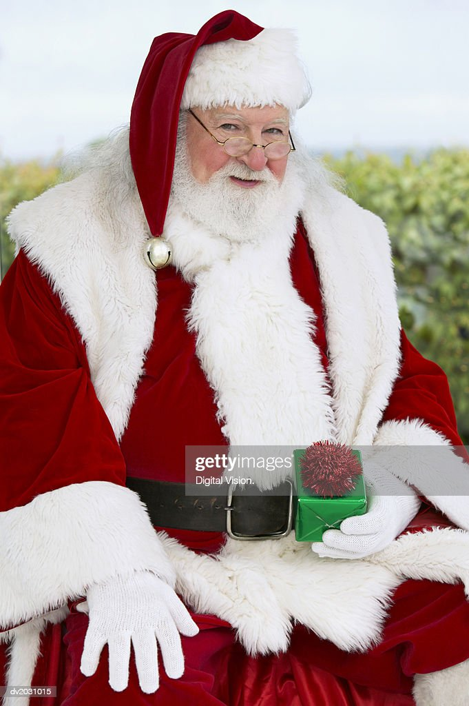 Portrait of a Man in a Santa Costume Holding a Wrapped Gift : Stock Photo