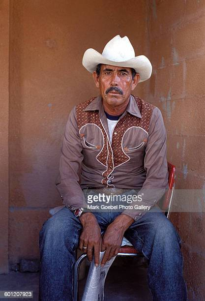 Portrait of a man in blue jeans a brown western shirt and a white cowboy hat Juarez Mexico late 1980s