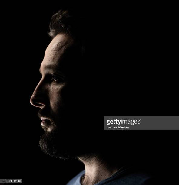 portrait of a man in dark background - profile stock pictures, royalty-free photos & images