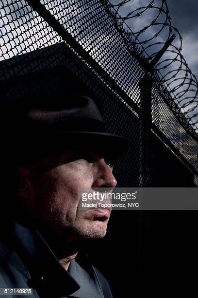 Portrait of a man in hat against barbed wire fence