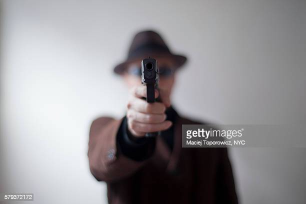 Portrait of a man in hat aiming handgun at the camera.