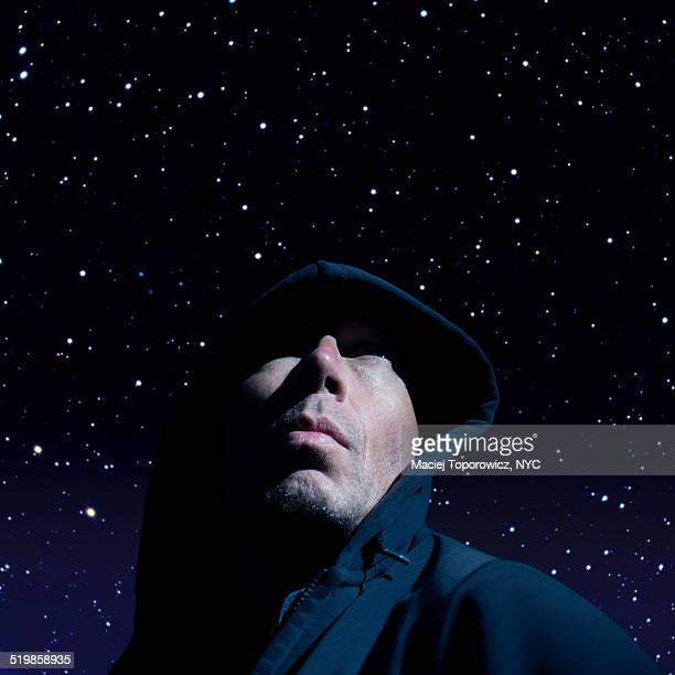 Portrait of a man in hood against starry sky.