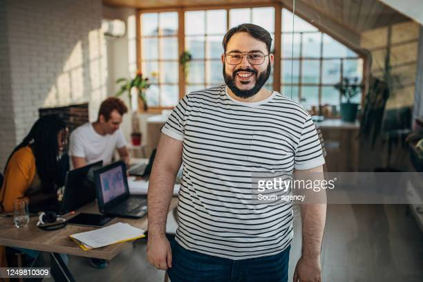 portrait of a man in small modern office - businesswear stock pictures, royalty-free photos & images