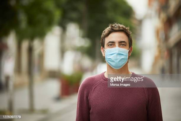 portrait of a man in the city wearing protective face mask - protective face mask stock pictures, royalty-free photos & images