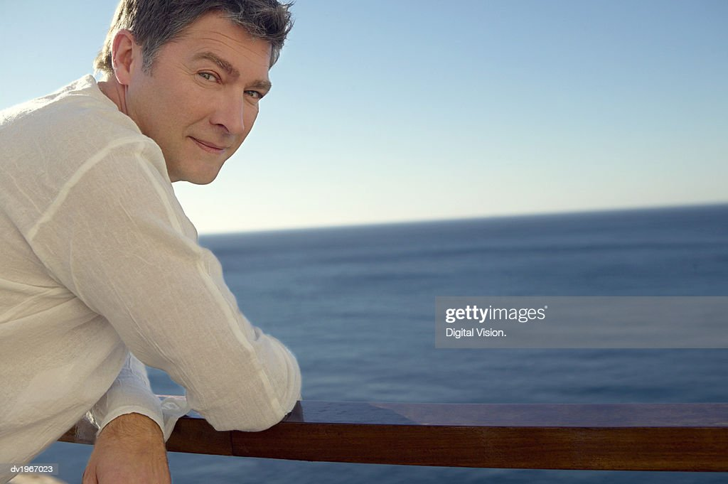 Portrait of a Man Leaning on a Railing by the Sea : Stock Photo