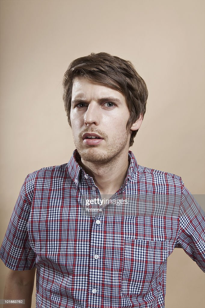 Portrait of a man looking confused, studio shot : Stock Photo