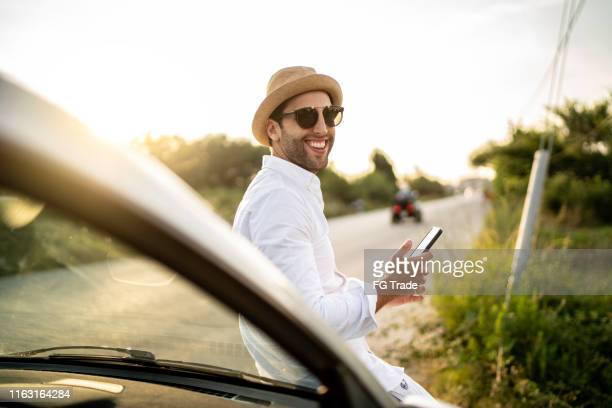 portrait of a man looking over should and using cellphone in front of car in a road - pardo brazilian stock pictures, royalty-free photos & images