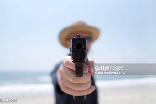 Portrait of a man on a beach aiming gun at the camera.
