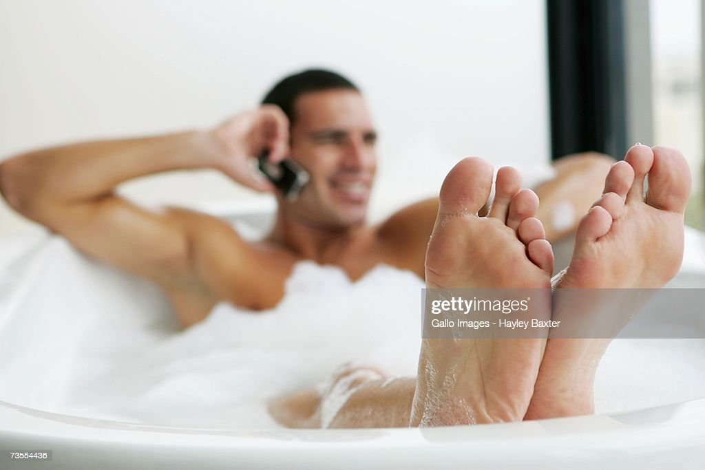 Portrait Of A Man On A Mobile Phone In The Bath