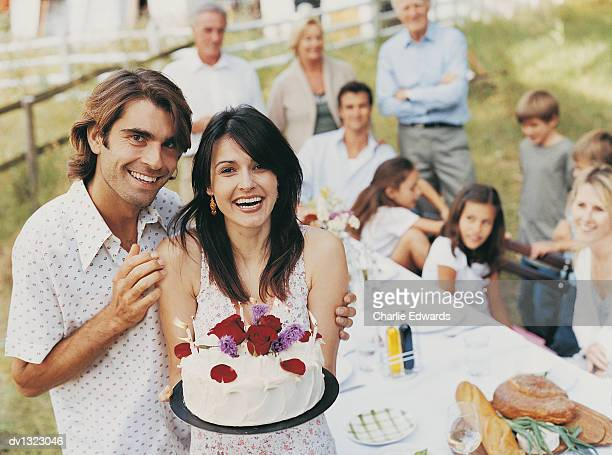 Portrait of a Man Outdoors With His Arm Around a Woman Holding a Birthday Cake and Family in the Background Sitting at a Table