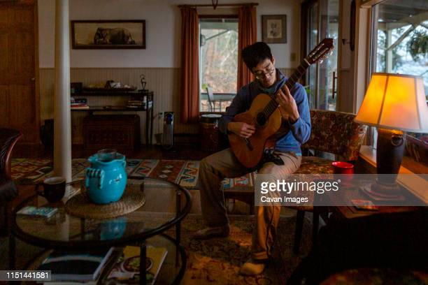 portrait of a man playing guitar by himself in an eclectic home - chitarra classica foto e immagini stock