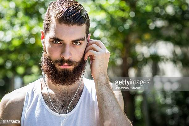 portrait of a man putting in a headphone - hairy chest stock photos and pictures