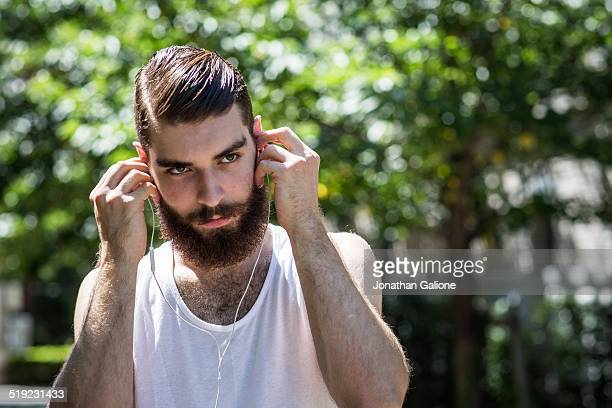 Portrait of a man putting in headphones