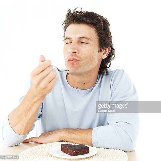 portrait of a man savoring a brownie with his eyes closed - genot stockfoto's en -beelden