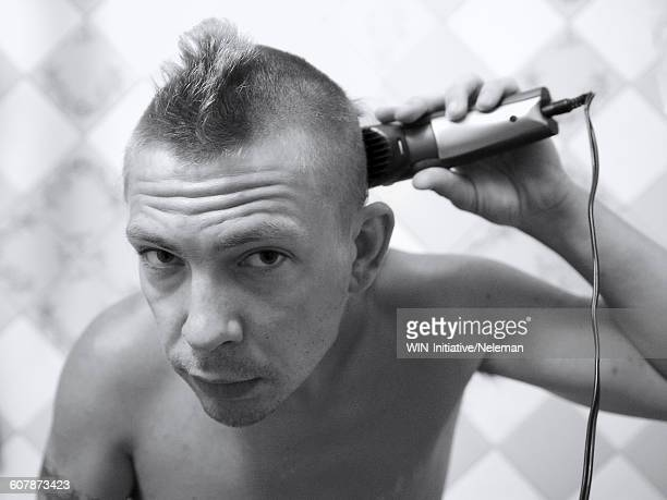 Portrait of a man shaving with an electric razor