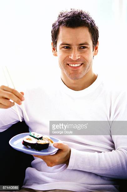 portrait of a man sitting and eating sushi with chopsticks