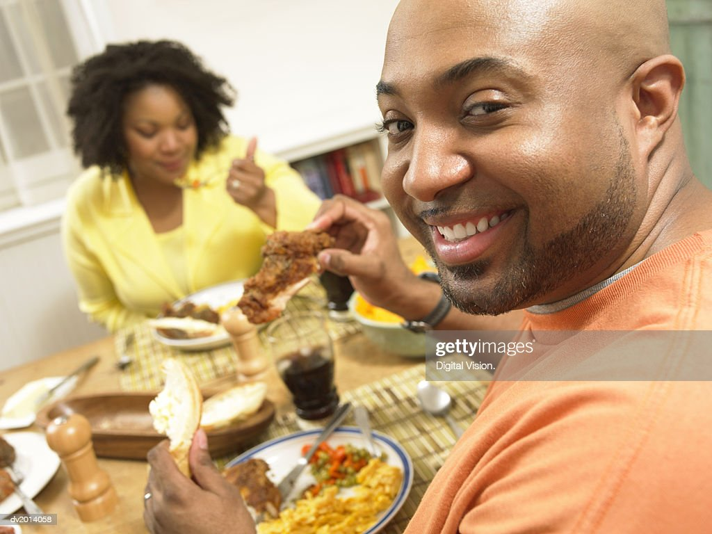 Portrait of a Man Sitting at the Table for Dinner Opposite His Wife, Holding a Chicken Drumstick : Stock Photo