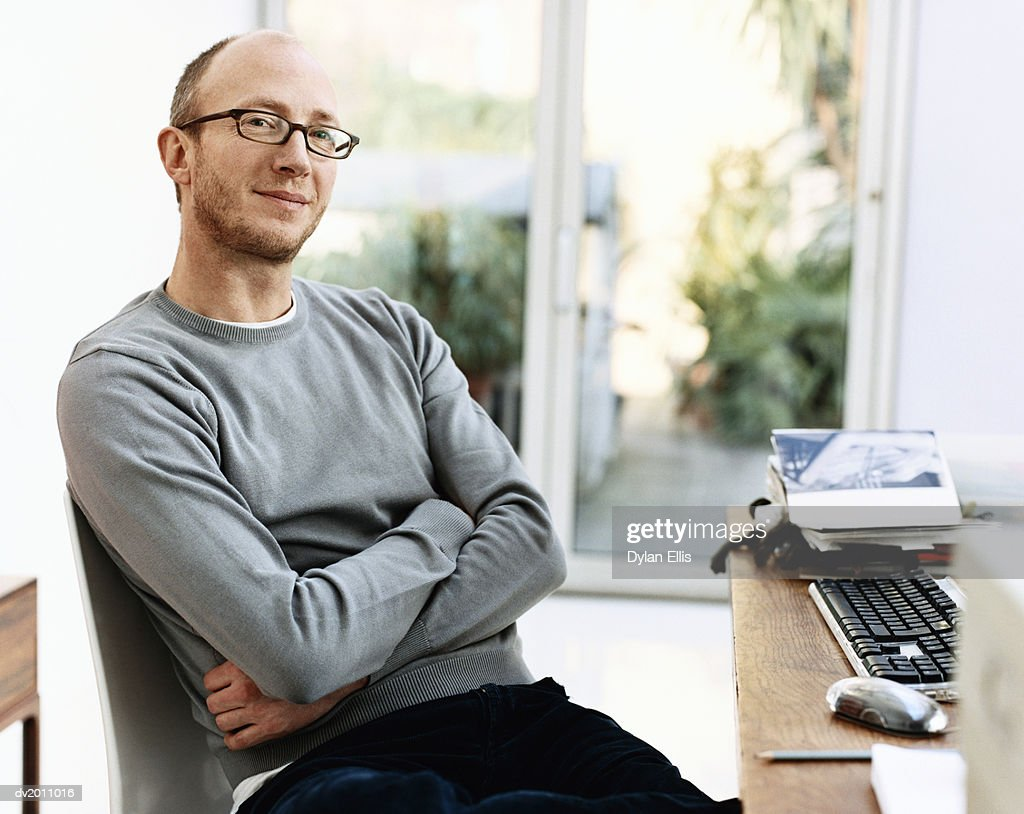 Portrait of a Man Sitting in a Chair By His Desk With His Arms Crossed at Home : Stock Photo