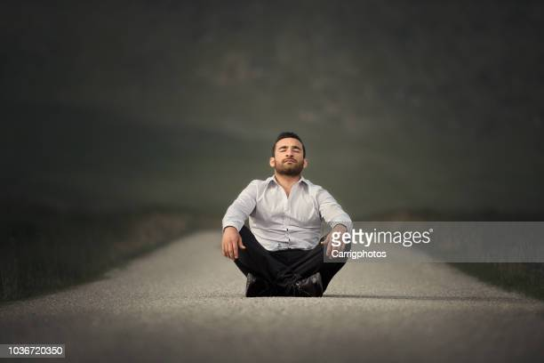 portrait of a man sitting in the middle of a path meditating, ireland - 胡坐 ストックフォトと画像
