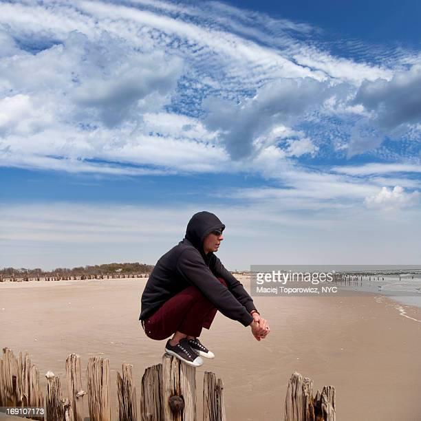 Portrait of a man sitting on a beach jetty.