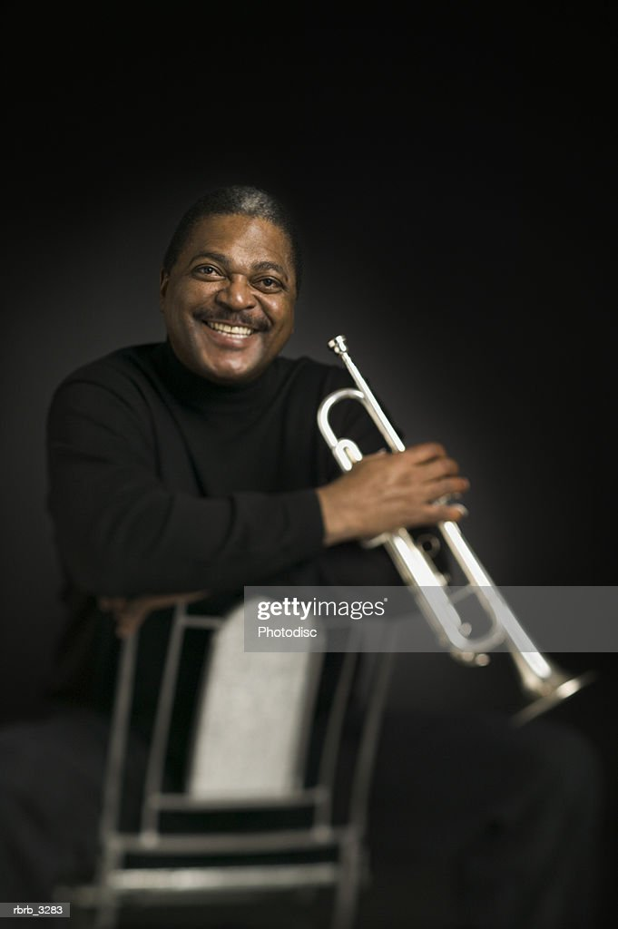 Portrait of a man sitting on a chair holding a trumpet : Foto de stock
