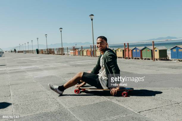 Portrait of a man sitting on a skateboard smiling