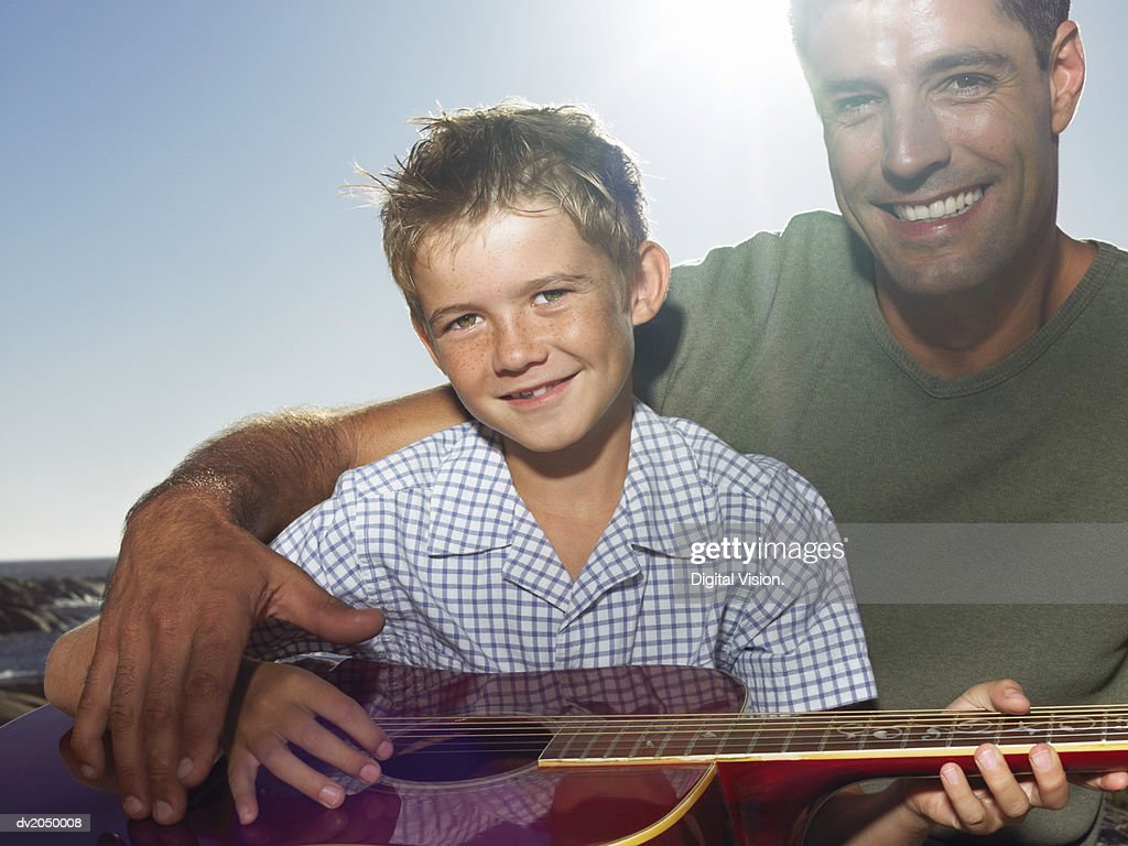 Portrait of a Man Sitting with His Arm Around a Boy Holding an Acoustic Guitar : Stock Photo