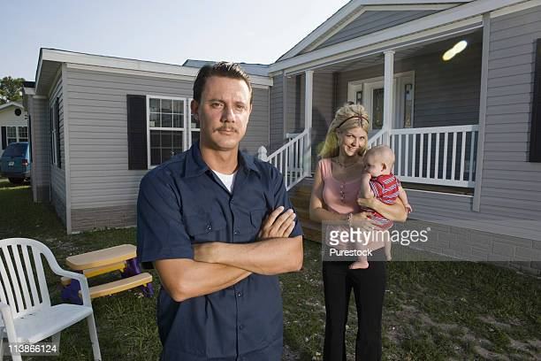 Portrait of a man standing in front of a trailer home with wife and baby
