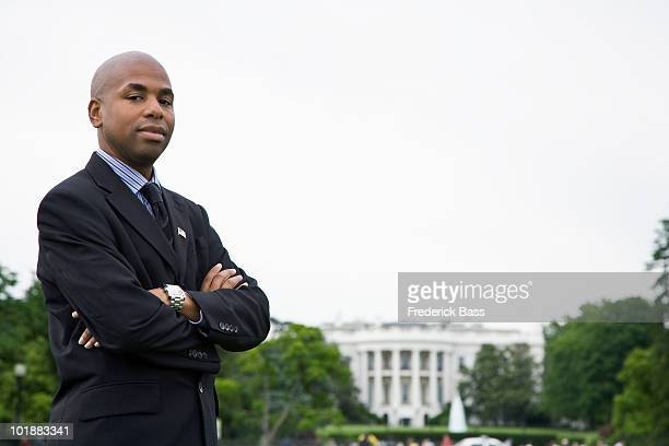 Portrait of a man standing in front of the White House, Washington DC, USA