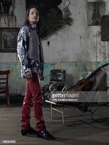 portrait of a man standing next tot a chair - leather shirt stock pictures, royalty-free photos & images