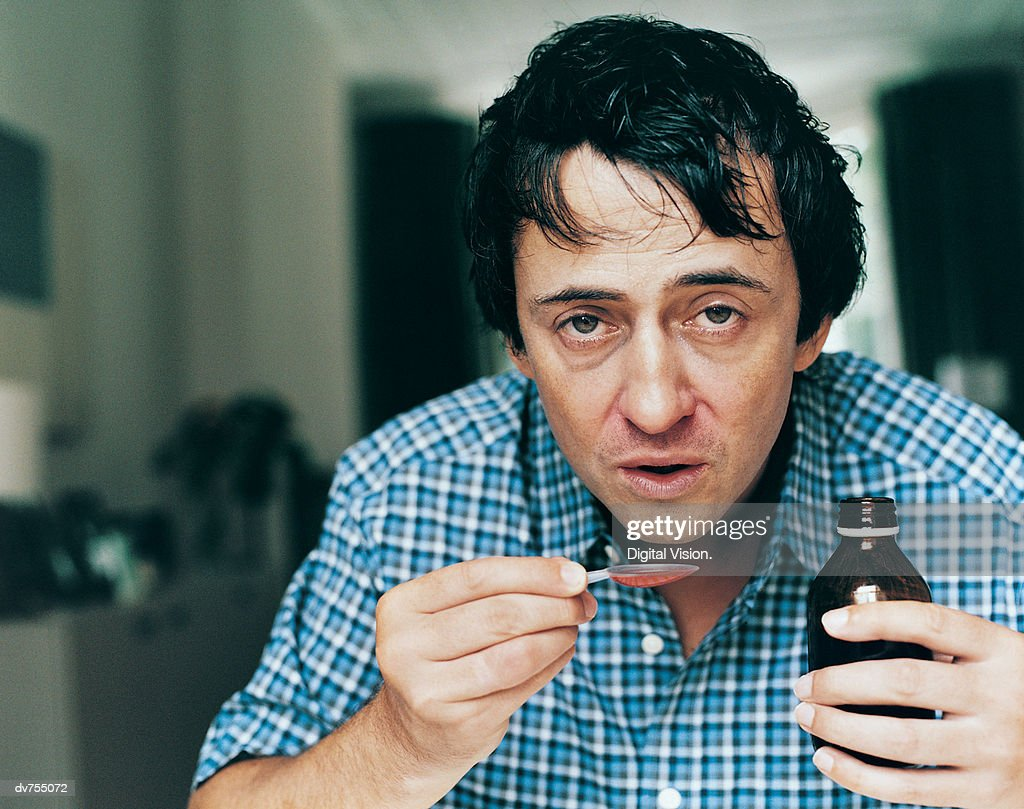 Portrait of a Man Taking Cough Medicine : Stock Photo