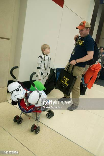 Portrait of a man two children, one in a stroller and the other dressed as a 'Stormtrooper,' at the Star Wars Celebration event at Wintrust Arena,...