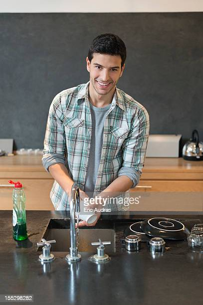 Portrait of a man washing dishes in the kitchen
