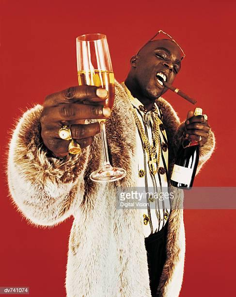 portrait of a man wearing a fur coat, holding a glass of champagne - casaco de pele - fotografias e filmes do acervo