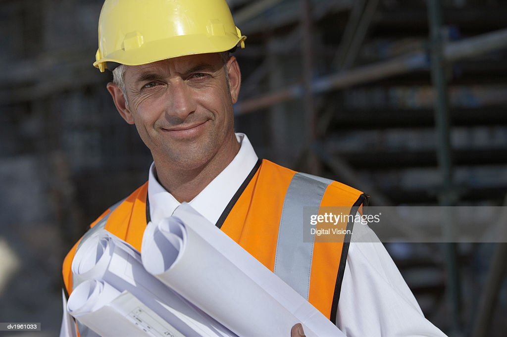 Portrait of a Man Wearing a Hard Hat and a Fluorescent Jacket, Holding Rolled Up Blueprints : Stock Photo