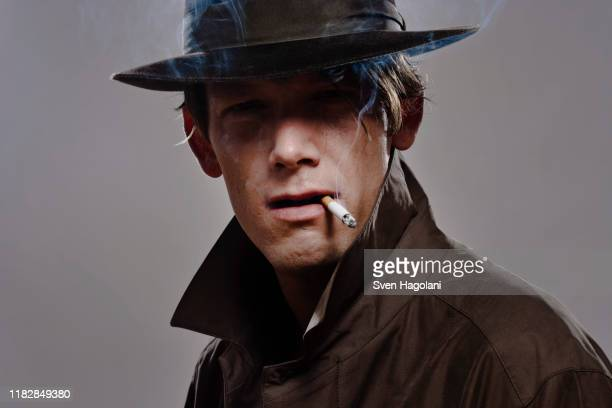 portrait of a man wearing a hat and trench coat while smoking - trench coat stock pictures, royalty-free photos & images