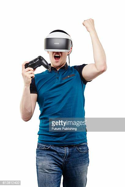 Portrait of a man wearing a PlayStation VR virtual reality headset and holding a DualShock 4 controller taken on August 9 2016