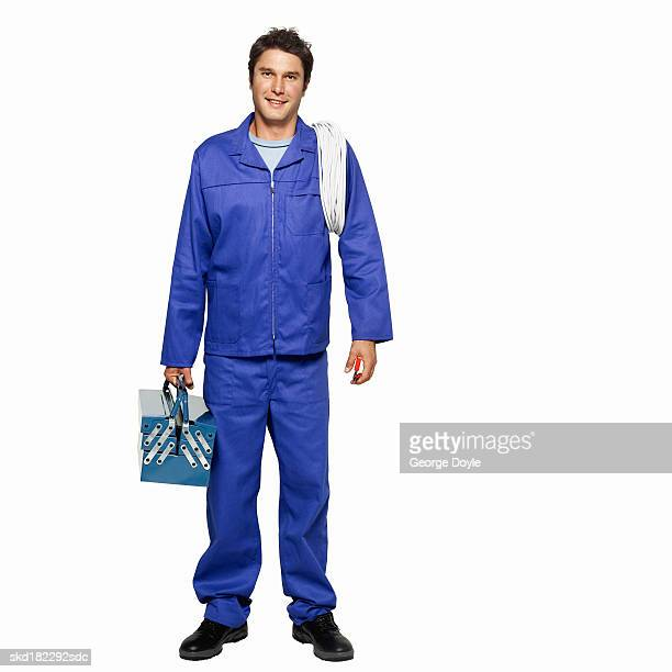 portrait of a man wearing overalls holding a tool box