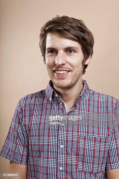 portrait of a man with a goofy smile, looking away, studio shot - nerd stock pictures, royalty-free photos & images