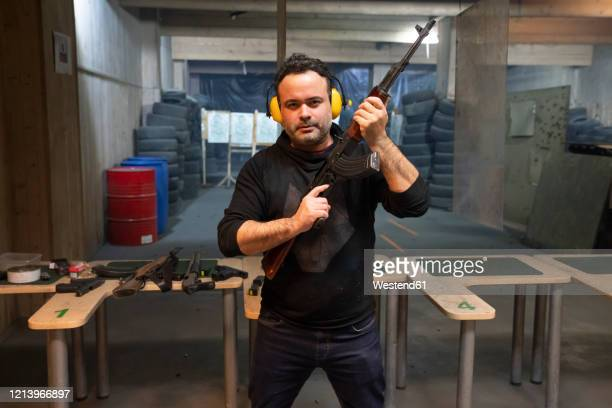 portrait of a man with a gun in shooting range - kalashnikov stock pictures, royalty-free photos & images