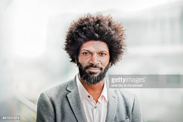 a portrait of a man with afro hair outside. - gray blazer stock pictures, royalty-free photos & images