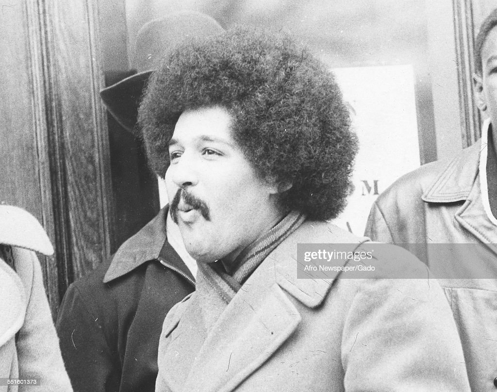 Portrait of a man with an Afro and moustache in a coat with other men, 1973.