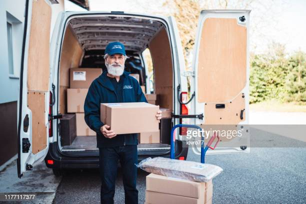 portrait of a man with delivery package - postal worker stock pictures, royalty-free photos & images